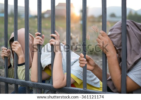 Concept immigrant crisis , Refugee peoples hand holding metal bar on refugee camp site - stock photo