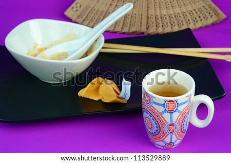 Concept is after-dinner tea in Chinese Restaurant.  Cup of tea with opened fortune cookie on black platter with empty soup bowl and spoon on purple background with carved bamboo fan and chopsticks.