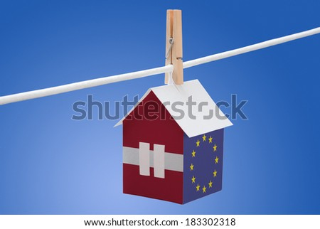 concept - Latvia, Latvian and EU flag painted on a paper house hanging on a rope - stock photo