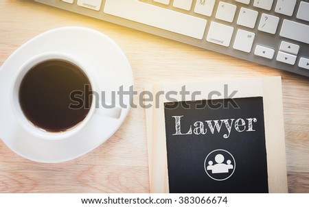 Concept Lawyer message on wood boards. A keyboard and a glass coffee table.Vintage tone. - stock photo