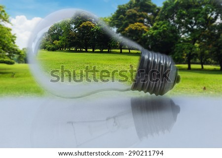 Concept , light bulb  with a green  grass and tree pictured inside on nature background - stock photo