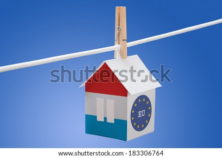 concept - Luxembourg and EU flag painted on a paper house hanging on a rope - stock photo