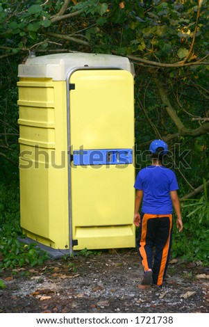 Concept: Modern Conveniences. A young girl walking towards a portable washroom in a nature reserve