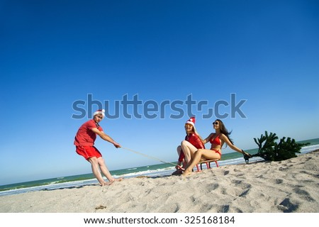 Concept: New Year on the beach. Man in Christmas hat on the beach pulling a sled with two girls and Christmas tree