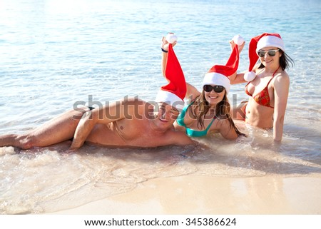 Concept: New Year on the beach. Two girls and a man on the beach in a red cap of Santa Claus