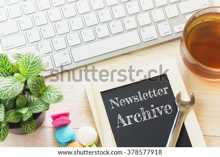 Concept Newsletter Archive message on wood boards. Macaroons and glass Tea on table. Vintage tone. - stock photo