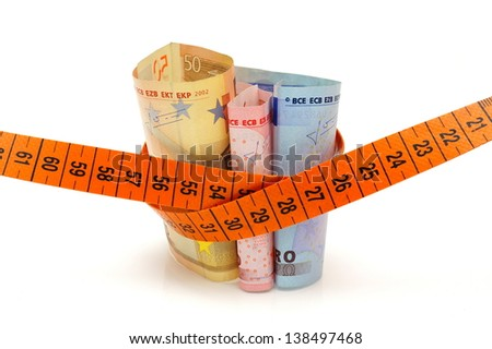 Concept od cutting cost with money and measuring tape - stock photo