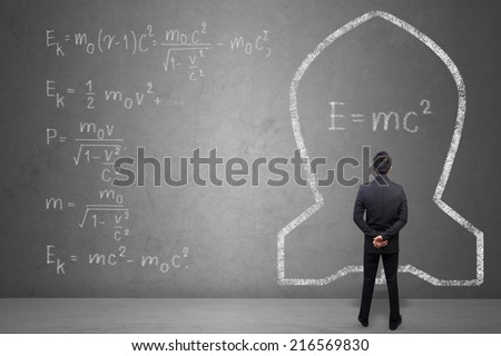 Concept of a businessman that solves problems of Albert Einsteins physical formula on concrete wall background - stock photo