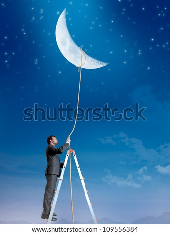 Concept of a businessman that wants the moon - stock photo