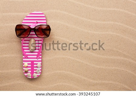 Concept of a woman's face, flip-flops and sunglasses on wavy in sand