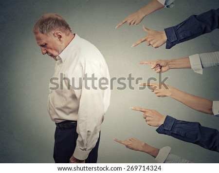Concept of accusation guilty businessman person. Side profile upset old man looking down many fingers pointing at him isolated grey office wall background. Human face expression emotion feeling  - stock photo