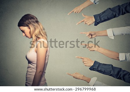 Concept of accusation guilty person girl. Side profile sad upset woman looking down many fingers pointing at her back isolated on grey office wall background. Human face expression emotion feeling - stock photo