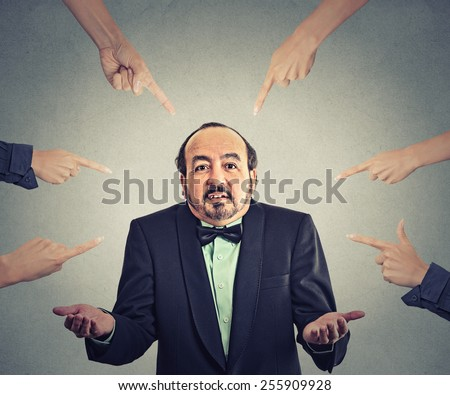 Concept of accusation of guilty arrogant businessman. Middle aged man judged by different people many women fingers point at him. Guy shrugs shoulders  - stock photo