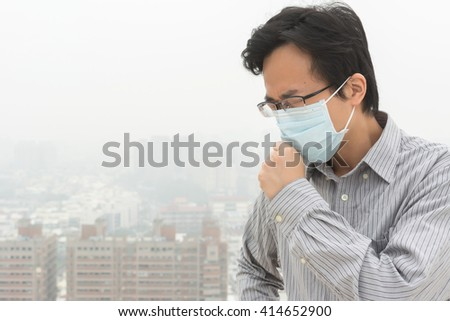 concept of air pollution with a Asian young man with a mask - stock photo