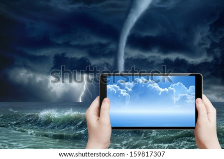 Concept of augmented reality, weather forecast - abstract tablet pc in hands, sunny weather, stormy weather, tornado on sea, dark stormy clouds, bright lightning