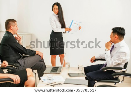 Concept of business meeting in the office. A group of people they listen to the report of the asian businesswoman, someone writes something or fill documents