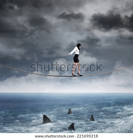 Concept of business risk with businesswoman walk on the rope above sea - stock photo