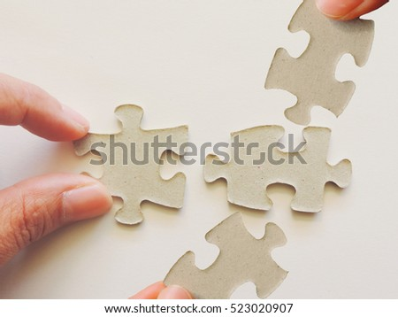 Concept of business teamwork and integration,hands hold puzzle on white background.