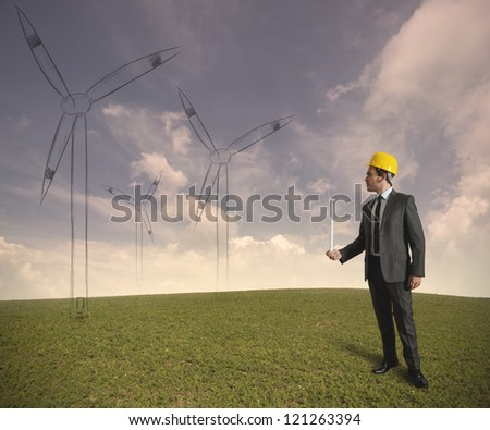 Concept of businessman that plans a wind turbine project - stock photo