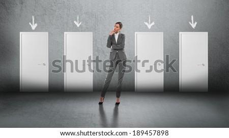 Concept of businesswoman choosing the right door - stock photo