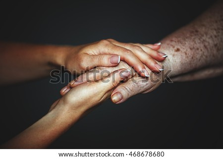 concept of care for older people and pensioners. Hands of the old and a young woman