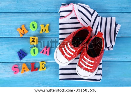 Concept of childish goods sale - bootees and T-shirts on blue wooden background - stock photo