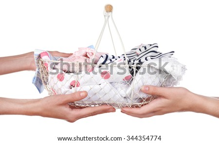 Concept of childish goods sale -one woman hand gives basket with clothes to another, isolated on white background