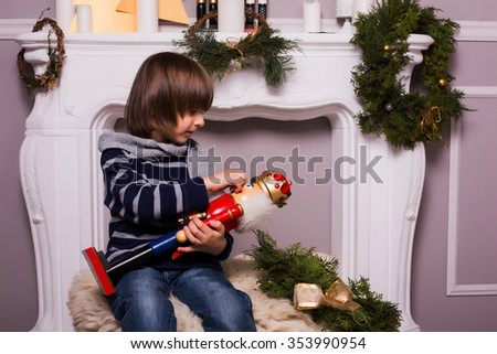 Concept of christmas holiday / Handsome boy with toy on Christmas background