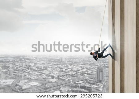 Concept of competition with businessman climbing office building with rope