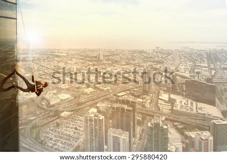 Concept of competition with businessman climbing office building with rope - stock photo