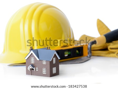 concept of construction a model house with construction tools isolated on a white background - stock photo