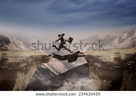 Concept of cooperation in business team. Woman runs above her partner for past the gap - stock photo