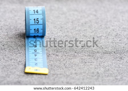 Concept of craft, skills, sewing and clothes making: roll of blue measuring tape on light grey background with copy space, selective focus