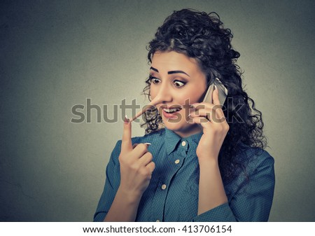 Concept of customer support representative liar with long nose. Portrait young woman talking on mobile phone telling lies isolated on gray wall background. Human face expressions  - stock photo
