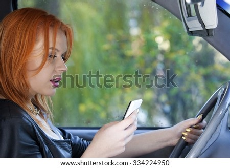 Concept of danger driving. Young woman driver red haired teenage girl texting on cell phone sending text reading message while driving the car. - stock photo