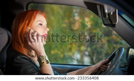 Concept of danger driving. Young woman driver redhaired girl talking on mobile phone smartphone while driving the car. - stock photo