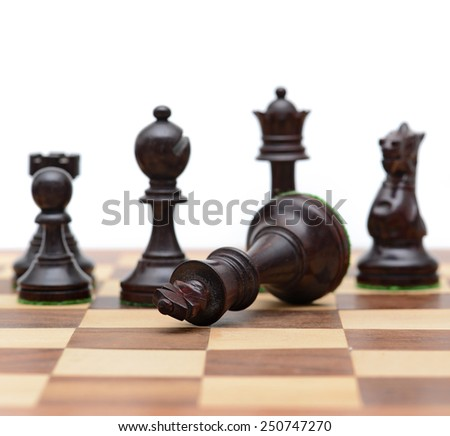Concept of defeat (fallen king, camera focus on black king chess piece, background blurred) - stock photo