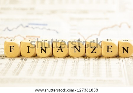 Concept of dices with letters forming word: Finanzen - German for Financials. On generic newspaper background with stock market numbers and some blurred charts.