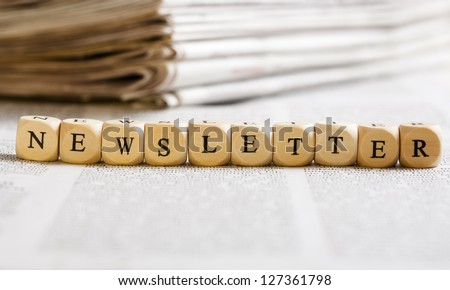 Concept of dices with letters forming word: Newsletter. Generic newspaper background with some blurred text on the bottom and paper stack in the back. Dices made from wood with natural imperfections. - stock photo