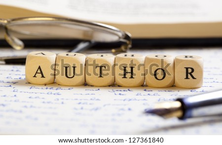 Concept of dices with letters forming words: Author. Generic handwritten text, pen, glasses and books as background.  Dices made from wood with natural imperfections. - stock photo