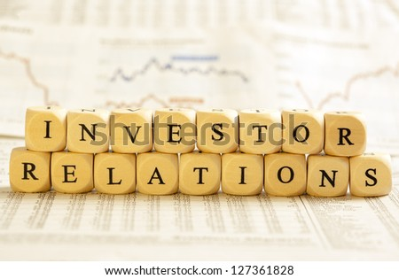 Concept of dices with letters forming words: Investor Relations. On generic newspaper background with stock market numbers and some blurred charts.  Dices made from wood with natural imperfections. - stock photo