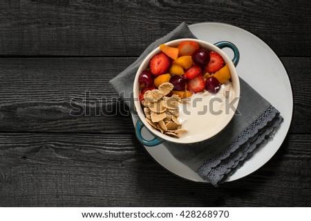Concept of diet and healthy eating. Cereal flakes with yogurt, strawberries, apricots, cherries in a bowl on old wooden table. Top view, space for text - stock photo