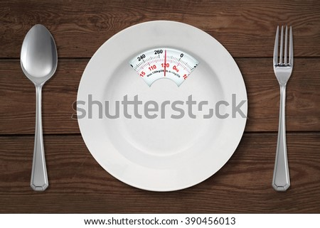 Concept of diet. Close up of empty plate shaped a scale with spoon and fork on the wooden table