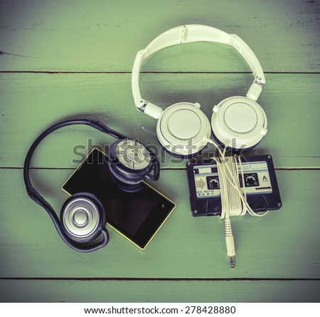 Concept of different technology between Smartphone cassette tape and headphone all were on the wood board  - stock photo