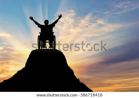 Concept of disability and disease. Silhouette happy disabled person in a wheelchair on the mountain