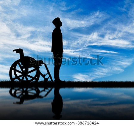 Concept of disability and disease. Silhouette of disabled and wheelchair daytime and reflection in water