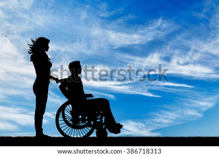 Concept of disability and disease. Silhouette of disabled person with a guardian against the sky