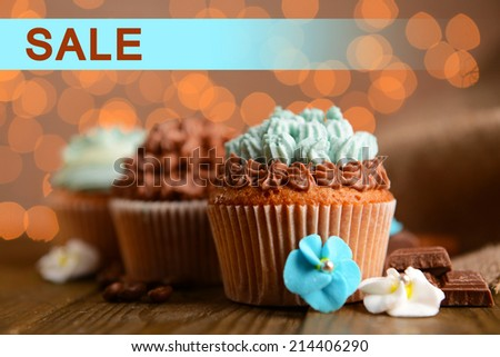 Concept of discount. Tasty cupcakes with butter cream on lights background - stock photo