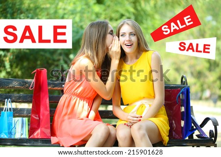 Concept of discount. Two beautiful young woman with shopping bags at park - stock photo