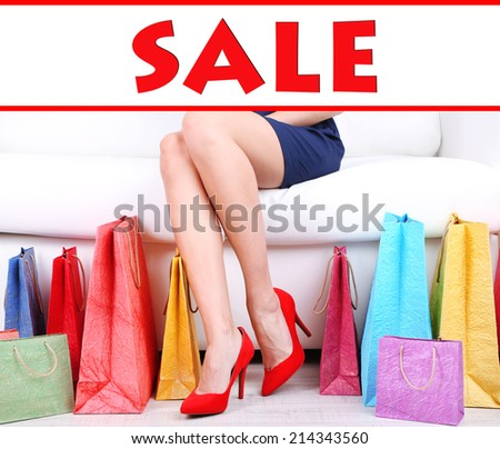 Concept of discount. Woman in red shoes sitting on sofa with shopping bags - stock photo